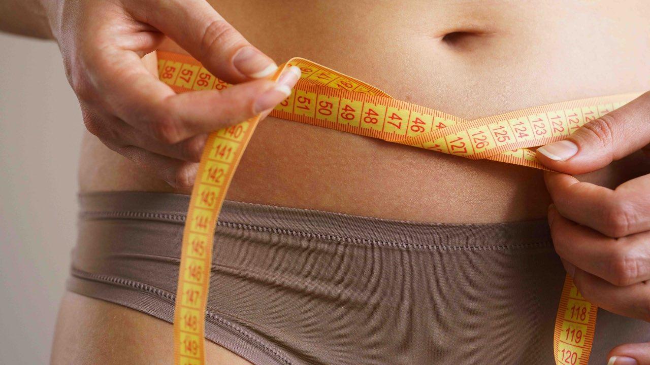 Une femme mesure son tour de taille avec un mètre.