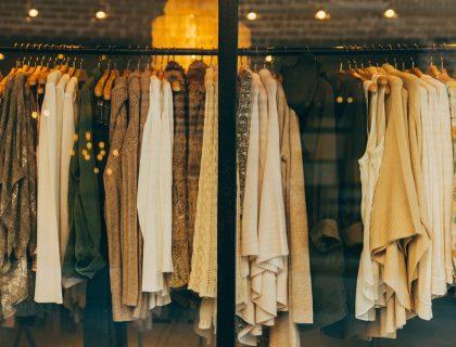 Plusieurs types de tuniques différentes sur un portant dans un magasin.