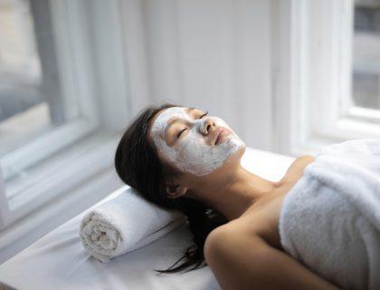 Jeune femme allongée profitant d'un masque beauté maison.